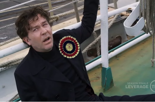 Nate is handcuffed to a railing, looking exhausted and cynical, a big tricolor rosette photoshopped onto his lapel