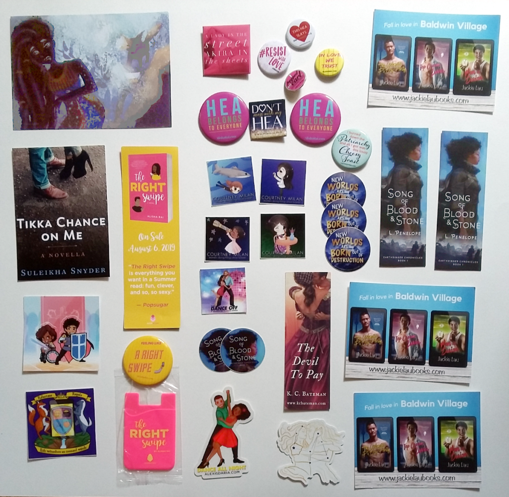 Selection of postcards, stickers, bookmarks, buttons, and more. Authors include Courtney Milan, Alyssa Cole, Jackie Lau, Suleikha Snyder, Alexis Daria, Alisha Rai, Olivia Waite, L. Penelope, and K.C. Bateman.